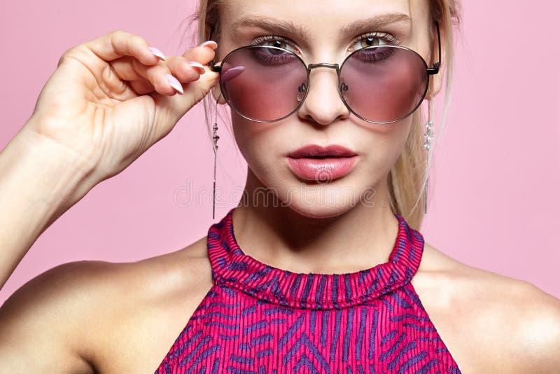 一微笑的可爱的年轻女人的画象被设色的玻璃的在桃红色背景 免版税图库摄影