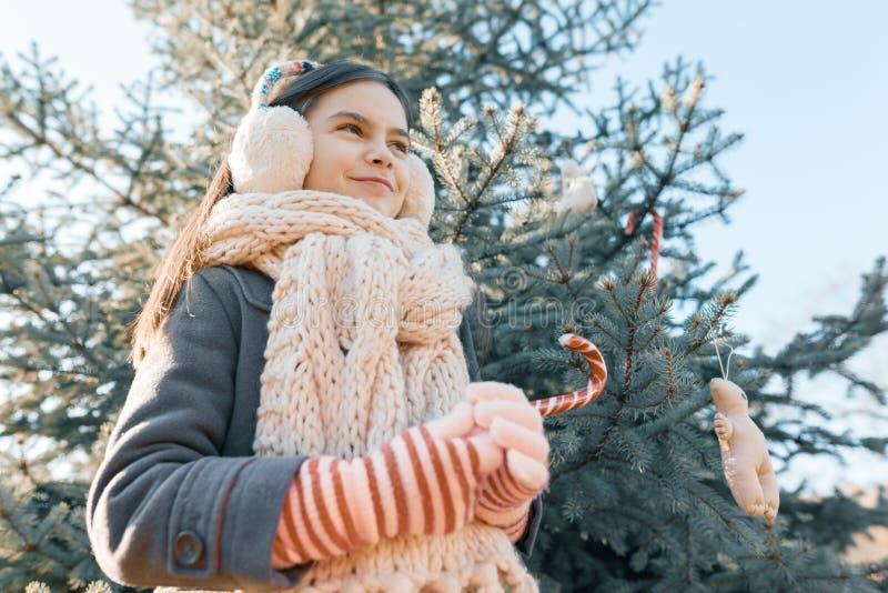 一微笑的女孩的室外冬天画象在圣诞树与传统棒棒糖,金黄小时附近的 库存图片