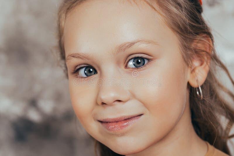 一微笑的少女的画象一件红色礼服的和有一种美好的发型的 E 免版税库存图片