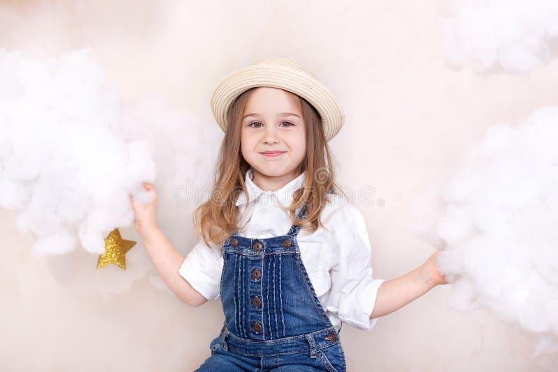 一微笑的逗人喜爱的女孩在与云彩和星的天空飞行 一点天文学家小旅客 学龄前edu的概念 免版税库存照片