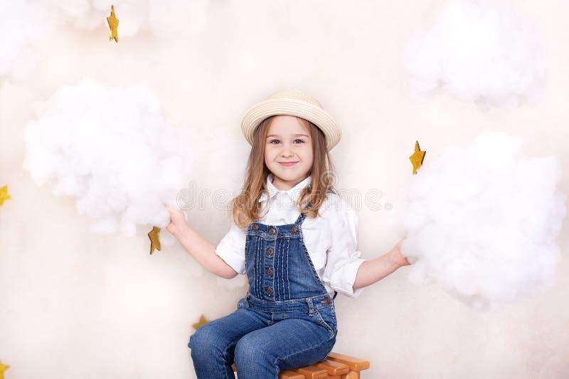 一微笑的逗人喜爱的女孩在与云彩和星的天空飞行 一点天文学家小旅客 学龄前edu的概念 免版税库存图片