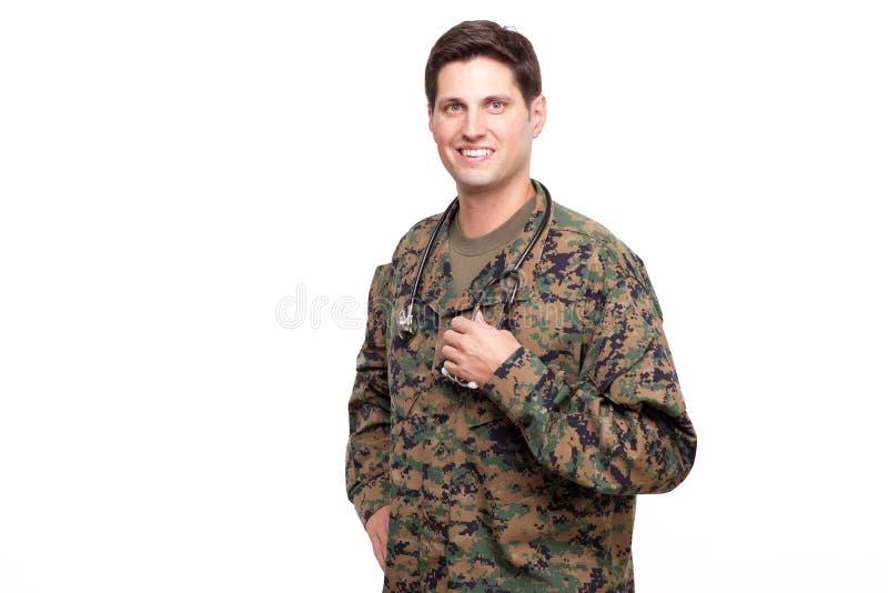 一微笑的年轻军事医生摆在的画象 免版税图库摄影