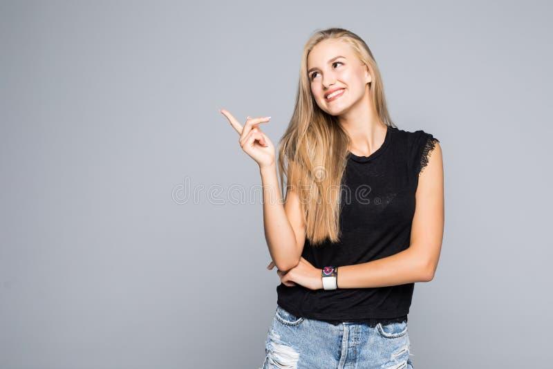一快乐和愉快的年轻美女的画象看与微笑照相机和指向手指的一件黑T恤杉的 免版税库存图片
