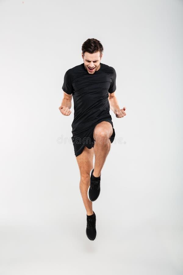 一快乐喜悦运动员跳跃的全长画象 免版税库存图片