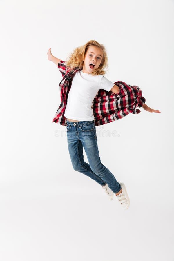 一快乐小女孩跳跃的全长画象 库存照片