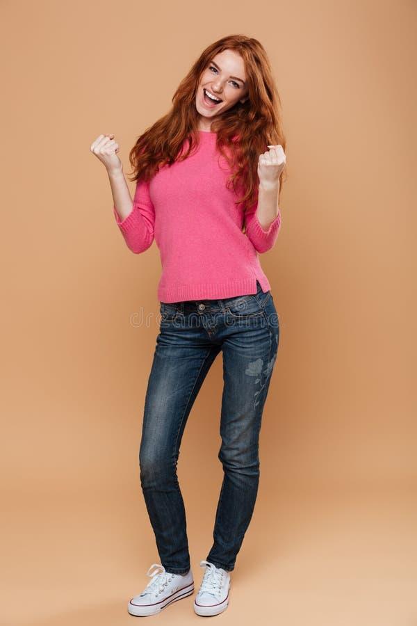 一快乐年轻红头发人女孩庆祝的全长画象 库存照片