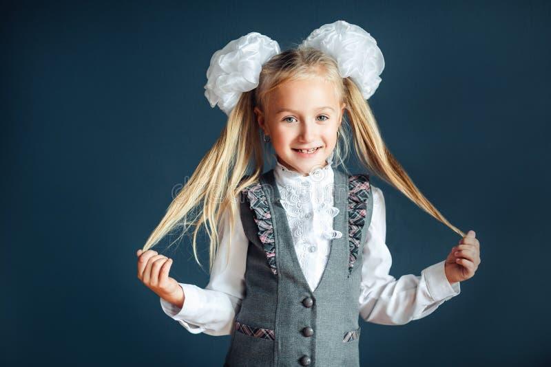 一快乐的女孩的特写镜头画象有白色弓的在蓝色背景 调查照相机的儿童女小学生和 免版税图库摄影