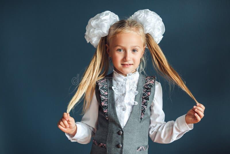 一快乐的女孩的画象有白色弓、白色女衬衫和灰色皮革的在蓝色背景 儿童女小学生看 免版税库存照片
