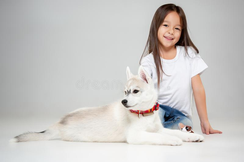 一快乐的女孩的画象获得与西伯利亚爱斯基摩人小狗的乐趣在地板上在演播室 免版税图库摄影
