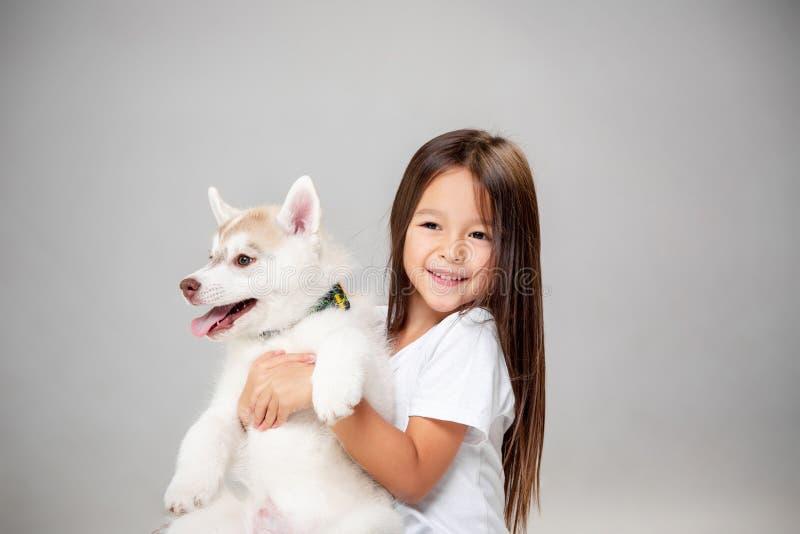 一快乐的女孩的画象获得与西伯利亚爱斯基摩人小狗的乐趣在地板上在演播室 库存图片
