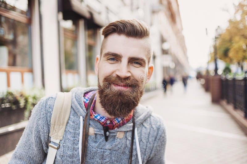 一快乐的微笑的年轻人的画象在城市街道上的 图库摄影