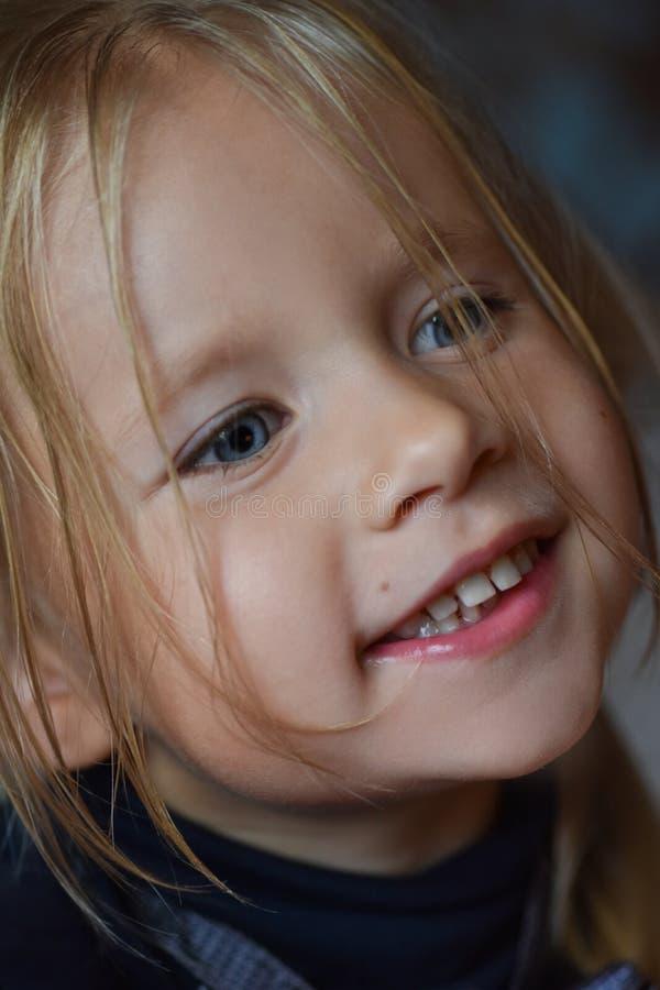一快乐的浪漫女孩和从东欧,特写镜头,黑暗的背景的开放微笑的画象有大蓝眼睛的 免版税库存图片