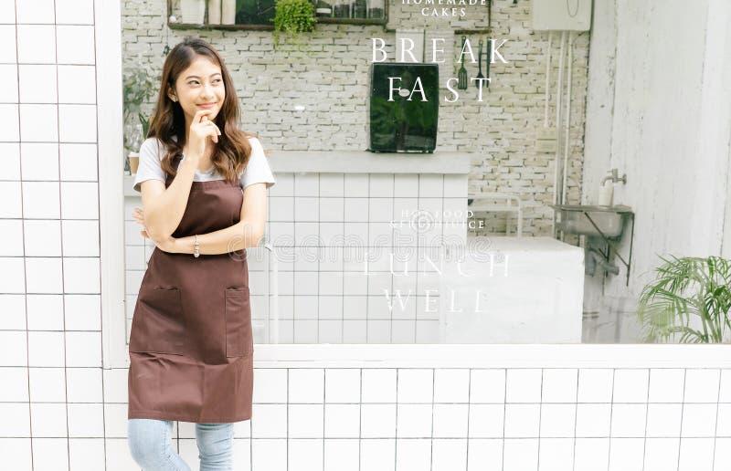 一愉快的年轻亚洲barista的画象在围裙的看和在她的小咖啡馆,腰部前面想出,拷贝空间 免版税库存图片