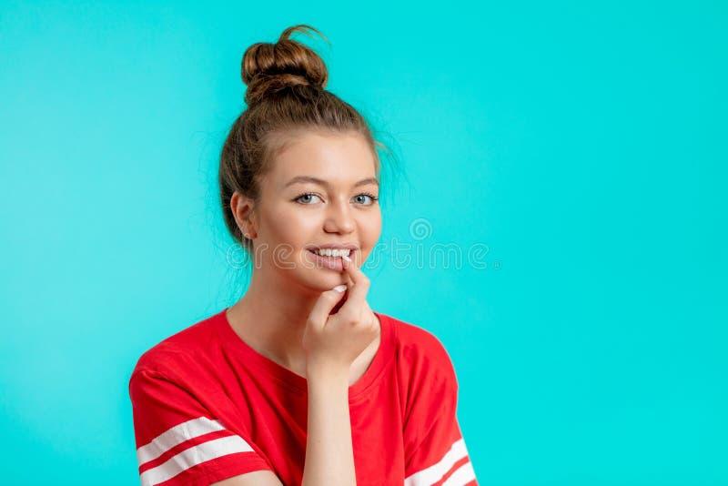 一愉快的年轻女人的接近的画象有一个手指的在她的嘴 免版税库存照片
