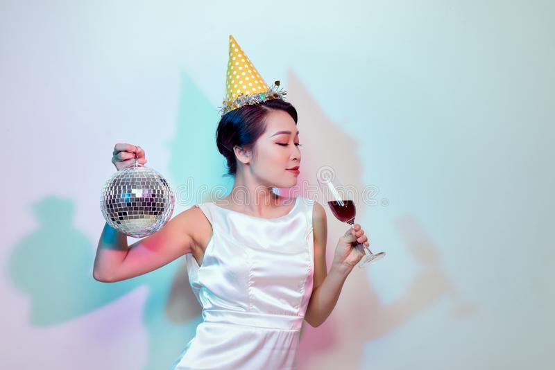 一愉快的美女的画象有党和喝香槟的白色礼服的,当站立与迪斯科球时 免版税库存图片