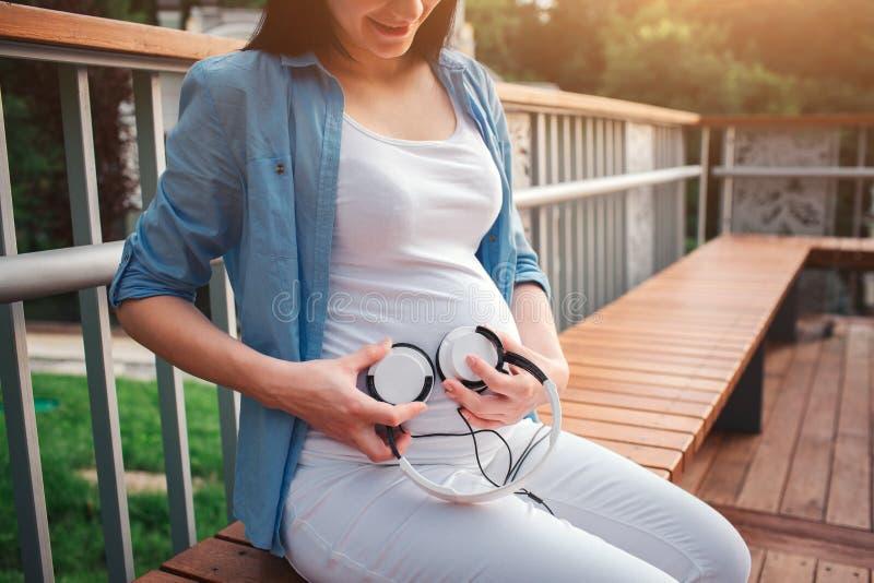 一愉快的黑色头发和骄傲的孕妇的画象在一个城市在背景中 她坐城市长凳 免版税库存照片