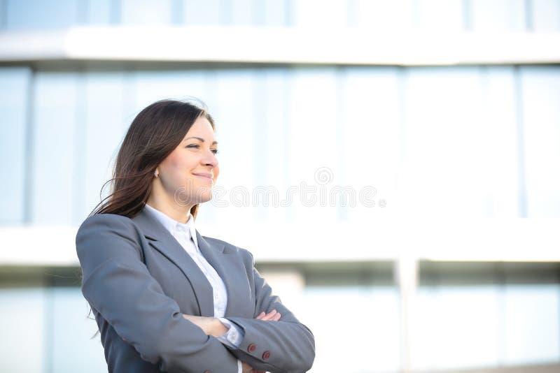 一成功女商人微笑的画象 在一个城市布局的美丽的幼小女性执行委员 免版税图库摄影