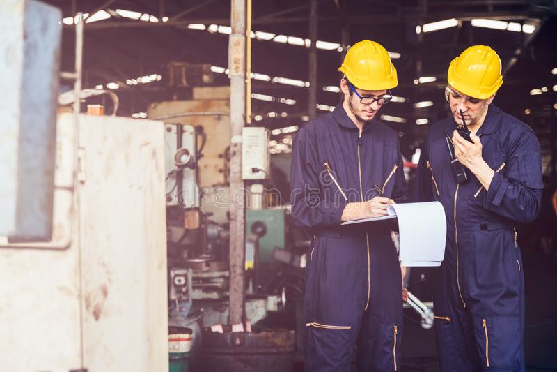 一批工厂维护工程师用对讲机检查继电保护系统 免版税库存图片