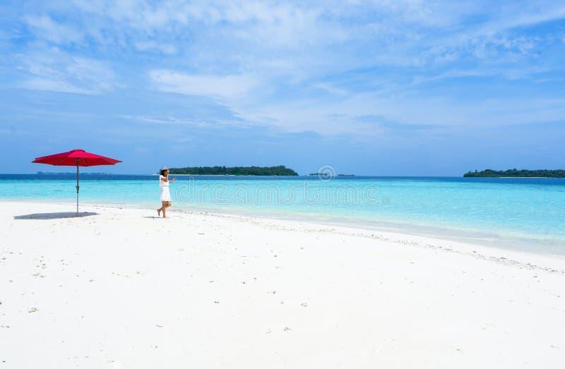 一把女孩和红色伞在海滩马尔代夫 免版税库存照片