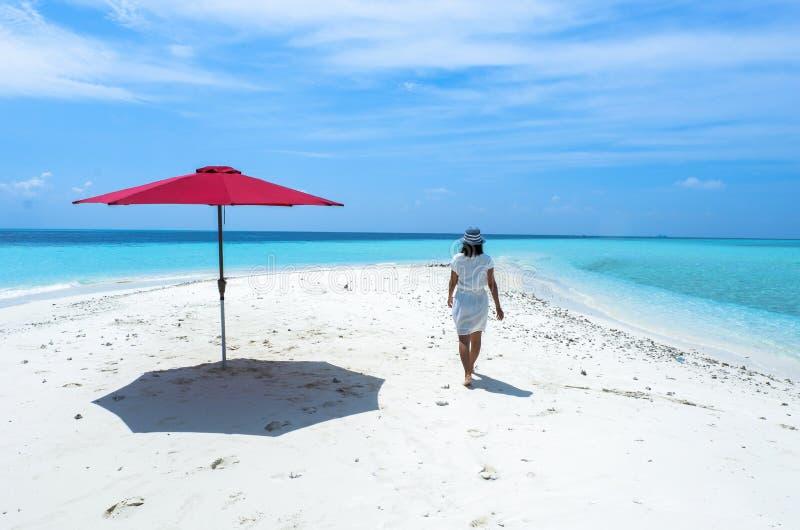 一把女孩和红色伞在海滩马尔代夫 库存图片