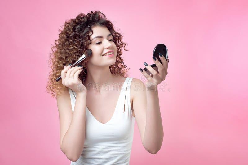 一把年轻白种人妇女藏品刷子的特写镜头和脸红调色板 库存图片