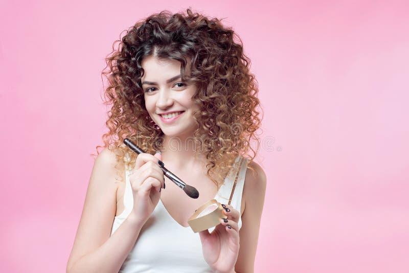 一把年轻白种人妇女藏品刷子的特写镜头和脸红调色板 免版税库存图片