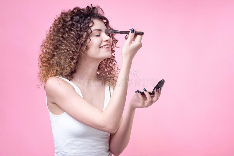 一把年轻白种人妇女藏品刷子的特写镜头和脸红调色板 库存照片