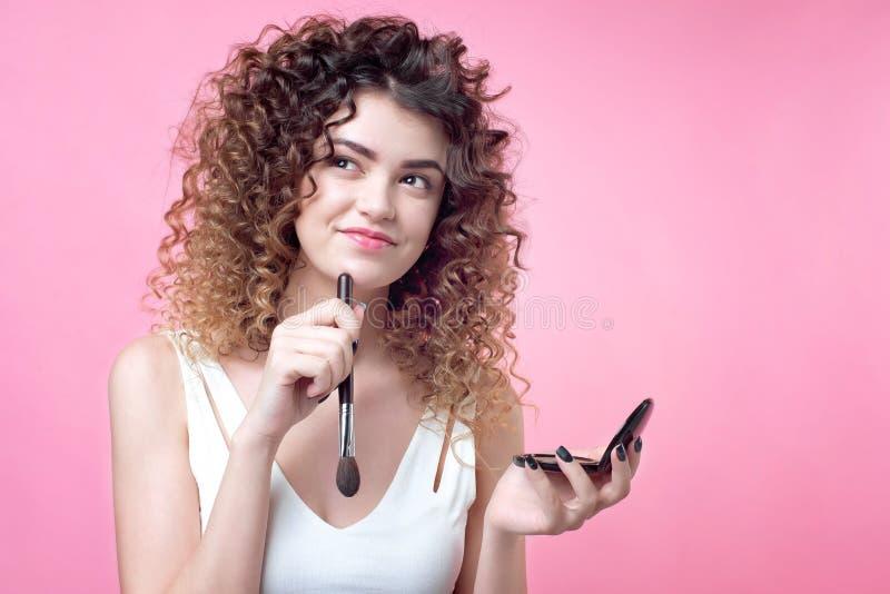 一把年轻白种人妇女藏品刷子的特写镜头和脸红调色板 免版税库存照片
