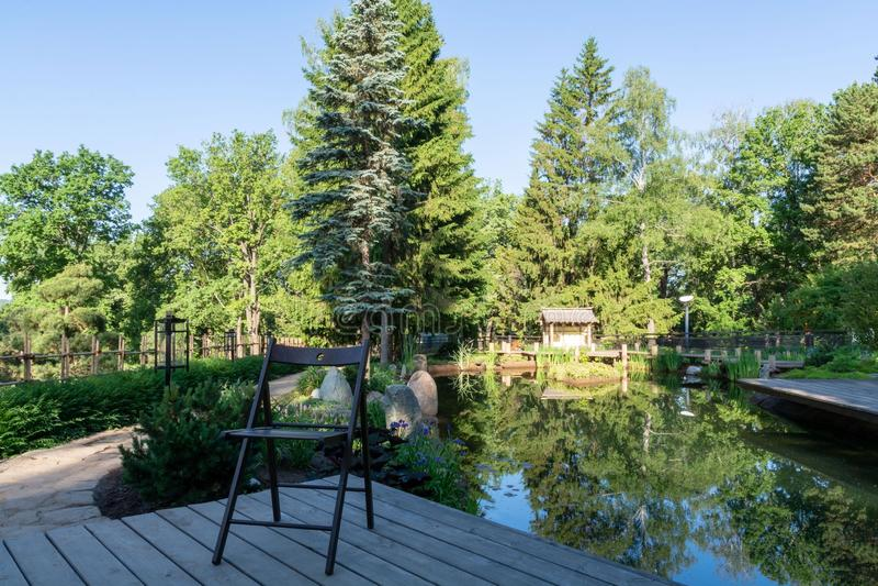 ?? 一把折叠的木椅子在木板甲板站立在一个小美丽如画的池塘前面的 免版税库存照片