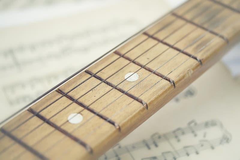 一把木吉他的概念性构成在背景活页乐谱老被染黄的和干净的纸的 库存照片
