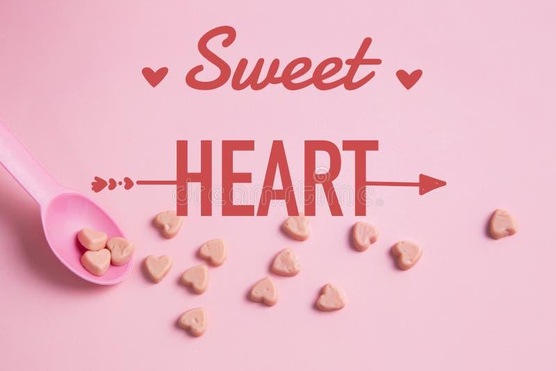 一把桃红色匙子用桃红色心脏糖果 免版税库存照片