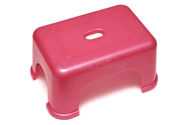 一把桃红色红色塑料凳子有四短的腿支持 免版税图库摄影