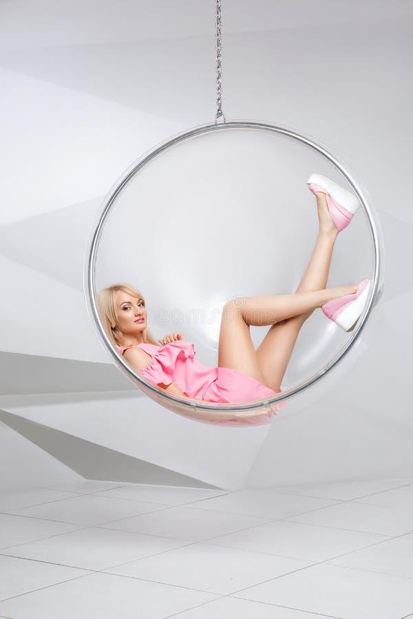 一把椅子的少妇在白色背景 几何 一件桃红色礼服的金发碧眼的女人在塑料圆的椅子 库存图片