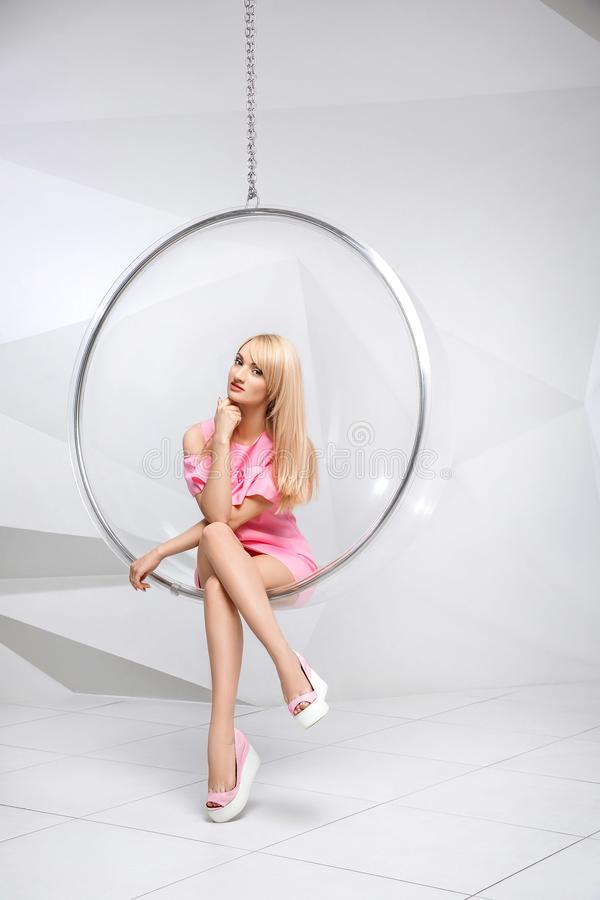 一把椅子的少妇在白色背景 几何 一件桃红色礼服的金发碧眼的女人在塑料圆的椅子 免版税图库摄影