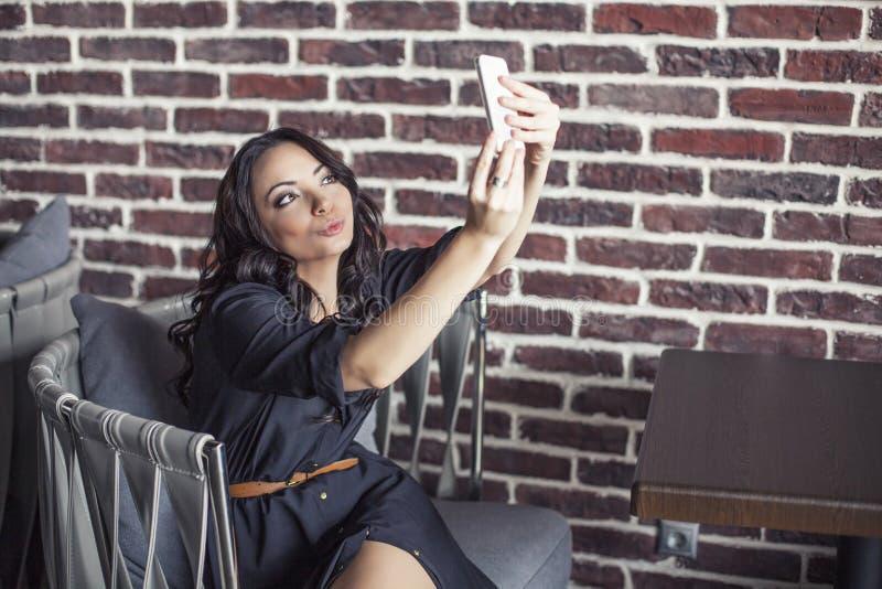 一把椅子的美丽的妇女在餐馆做selfie  免版税图库摄影