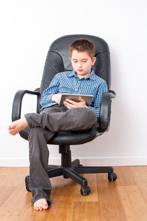 一把椅子的年轻英俊的男孩与片剂 库存图片