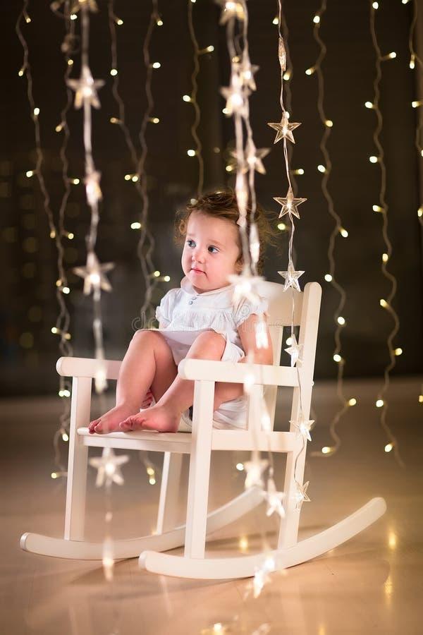 一把白色摇椅的可爱的小孩女孩在有圣诞灯的暗室 免版税库存图片