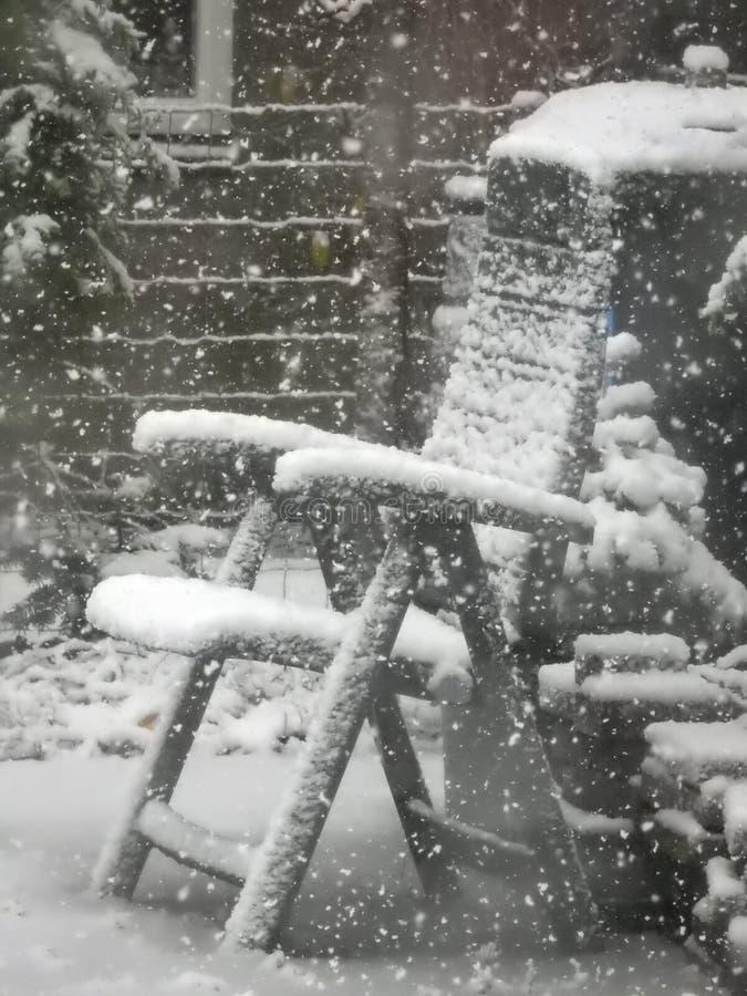 一把积雪的椅子在后院庭院里 图库摄影