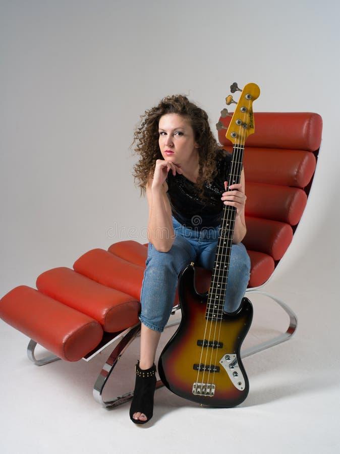 一把红色扶手椅子的卷曲女孩有吉他的 免版税图库摄影