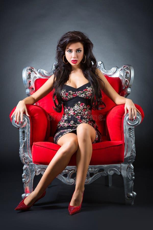 一把红色椅子的少妇 免版税库存图片
