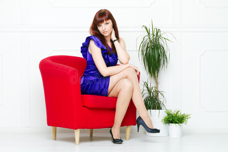 一把红色椅子的新美丽的妇女 免版税图库摄影