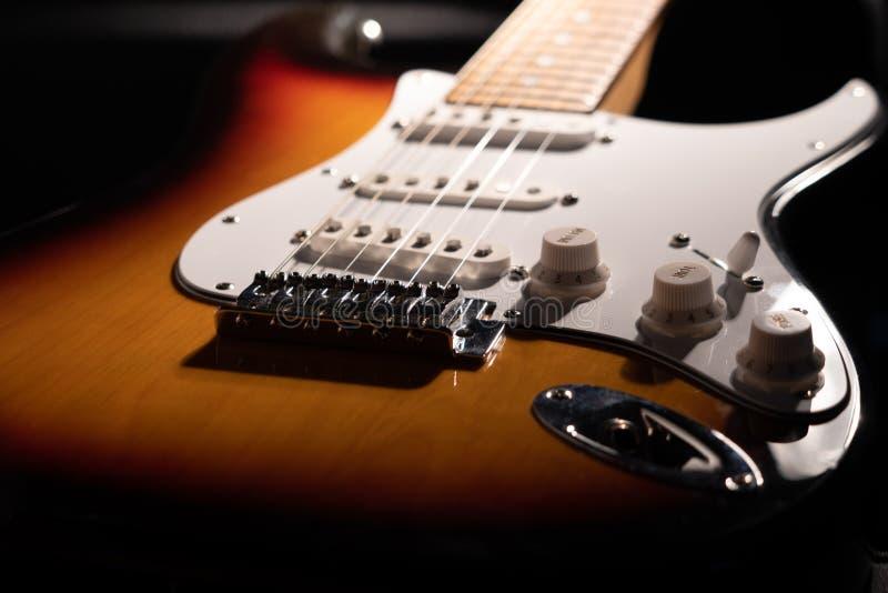 一把镶有钻石的旭日形首饰的电吉他的特写镜头 免版税库存照片
