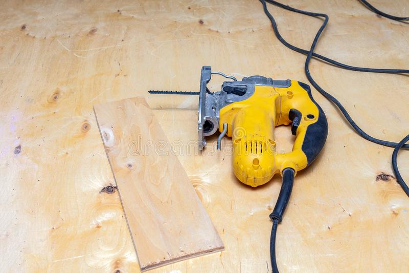 一把黄色电竖锯的Flatlay准备好为在工作凳的工作使用有被锯的胶合板的在木匠业工作的一个车间 工具 免版税库存图片