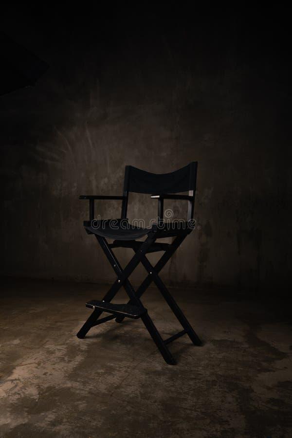 一把黑木椅子在照相馆站立反对背景 免版税库存图片