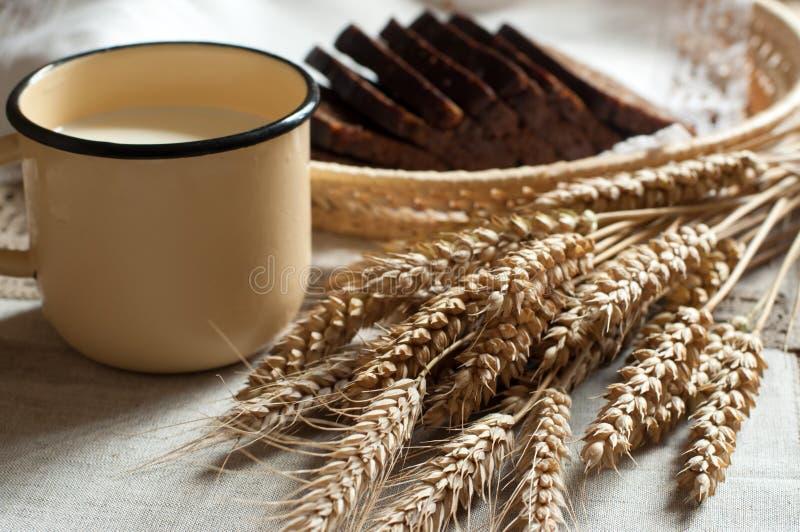 一抱耳朵、新鲜面包和一杯在秸杆盘子的牛奶有一张亚麻布餐巾的 免版税图库摄影