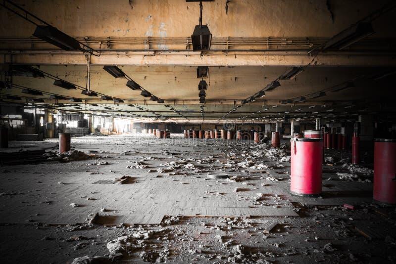 一排被放弃的工厂厂房的肮脏的工业内部 免版税库存照片