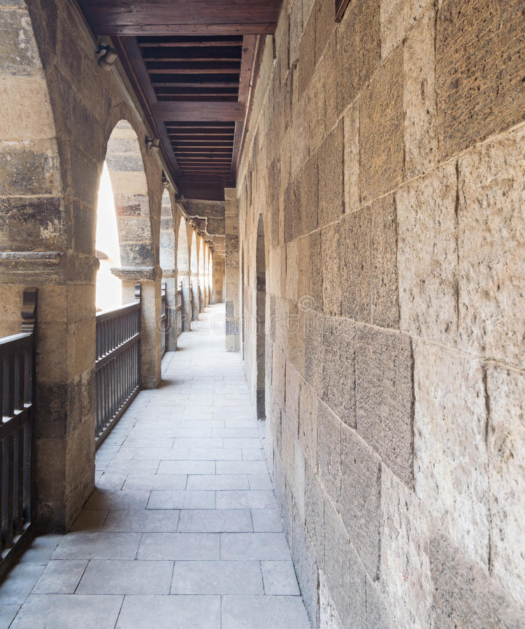 一曲拱角度图与被插入的木楼梯栏杆的在包围商队投宿的旅舍巴兹Wikala的庭院拱廊  免版税库存图片