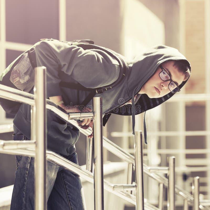 一有冠乌鸦的青少年的男孩在城市街道 免版税图库摄影