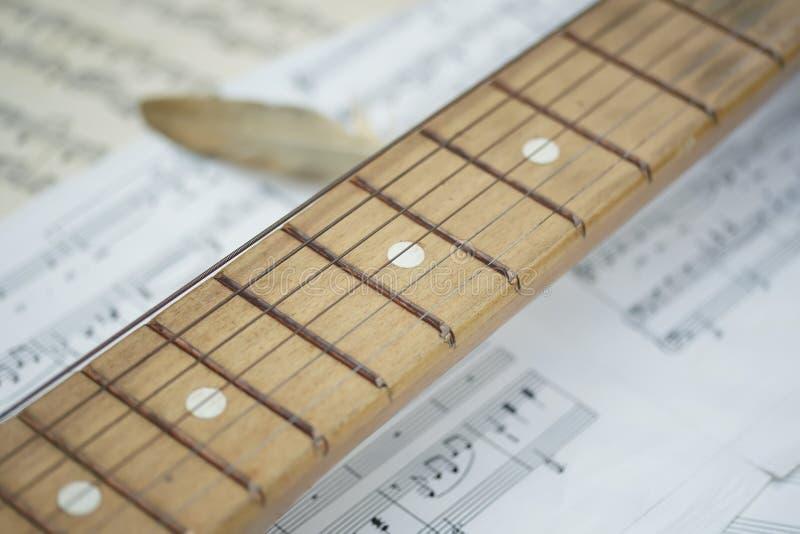 一木吉他soundboard和一根金黄羽毛l的概念性构成它在一个音乐和老被染黄的白纸说谎 免版税库存照片