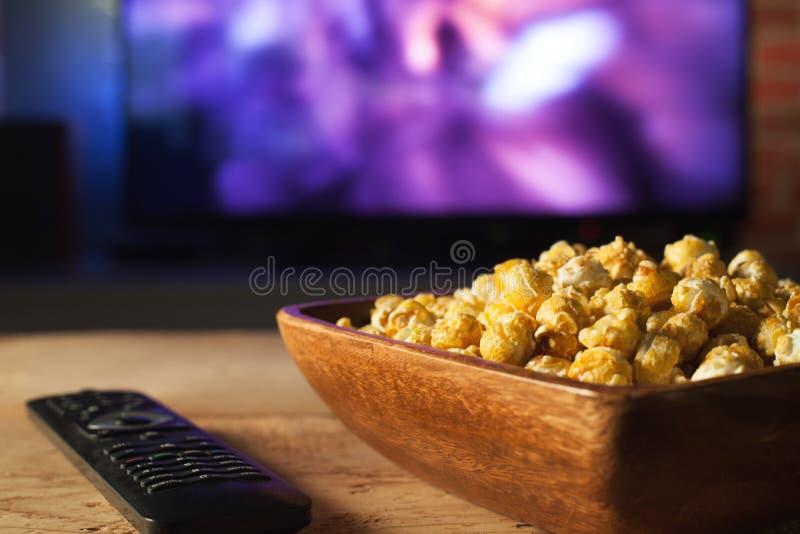 一木碗玉米花和遥控在电视运作的背景中 舒适在家观看电影或电视系列节目 库存图片